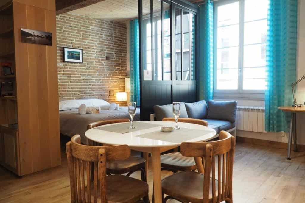 Holiday home in Toulouse: cosy interior with exposed wooden beams, traditional bricks, designer furniture